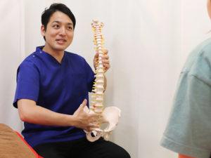 骨模型を持って話す施術者
